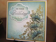 Poster: Michele G   Stamp is by Indigo Blu, stamped and embossed in gold. Flowers decoupaged. Background is sponged with Distress inks and spritzed with water mixed with mica powder.