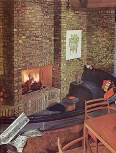 1970s conversation pit with fireplace in brick wall and curved sofa...  I could totally go for something like this