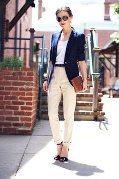 Dress in a deep navy blue blazer jacket and nude slacks to create a chic, glamorous look. Round off this look with black leather heeled sandals.   Black Sunglasses — White Tank — Navy Blazer — Black Leather Belt — cognac Leather Clutch — Beige Dress Pants — Black Leather Heeled Sandals