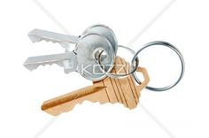 close-up image of metal gold and silver keys. - Close-up shot of gold and silver keys in key ring over plain white background.