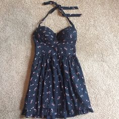 Guess black halter top dress Size 3 & 25 inches long The front has a small zipper in between the breast area. The cups have some padding. Dress zips on the side. The layers at the bottom of the dress along with the small flower print makes this uber girly !. Guess Dresses Mini