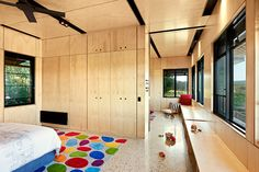 The Kids Pod interior is lined with plywood accentuated by matte black fittings and fixtures with polished concrete floors  | Kids Pod by Mihaly Slocombe (2014) | Merricks, Victoria, Australia | photo: Emma Cross