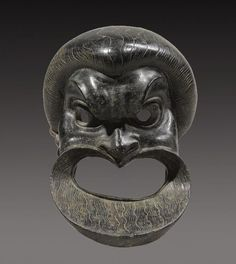 Roman bronze mask of a comic actor, 1st century A.D. With wide gaping mouth, flaring nostrils, large eyes beneath the gnarled brow, and finely incised wavy beard and hair, 16.5 cm high. Private collection