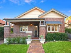 Brick californian bungalow house exterior with porch & window awnings - House Facade photo 522941
