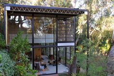 """""""Eames House, Case Study No. 8. This view of the west facade shows the 12-inch-deep joists that support the roof and are exposed inside. The house is organized around 7 1/2-foot-wide bays that are 17 feet high and 20 feet deep; one bay is outside on the west, but the rest are enclosed."""""""