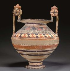 Daunian pottery nestoris, Daunian III, 550-400 B.C. Of buff colored fabric, the biconical body on a tall stem and disk foot, with a wide flaring rim, the high arching strap handles with rotellae at their peaks, the handles surmounted by large pomegranate-shaped finials and framed by raised points on either side at the shoulders, with orange, red and black painted ornament, the shoulders with bands of opposing triangles and crosshatching, 37.7 cm high. Private collection