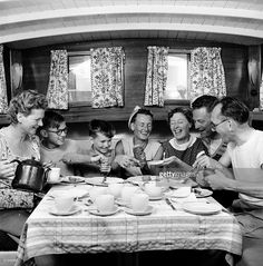 12th May 1957, A family squeeze into the cabin of their boat at teatime, during a sailing holiday on the Norfolk Broads.