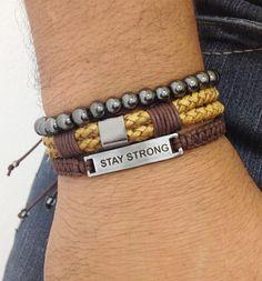 Kit de pulseiras masculinas (unissex), composto de 3 pulseiras sendo:  - 1 pulseira de couro trançado na cor marrom e detalhe metálico em banho grafite.  - 1 pulseira de pedra hematita de 6 mm em fio de silicone  - 1 pulseira shambala confeccionada em macramê com cordão encerado na cor café e pla...