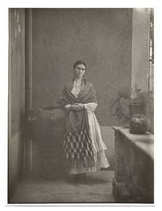* Frida Kahlo standing in a courtyard with a long shawl wrapped around her shoulders 1931 photo Photoprint studio San Francisco