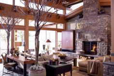 Contemporary living room design with a large stone fireplace and an open layout.