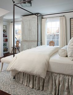 Plush pillows and deep bedcovers provide pure luxury for this girls bedroom.  The soft cream and misty blue palette create a chic, casual look that is easy to love. A custom-painted antique armoire adds personality. Marianne Jones LLC Marianne Jones - Birmingham, MI