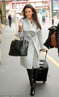 Wrapped up: Michelle wore a chic and cosy outfit of a wraparound grey coat, leather long boots and a black tote bag as she met fiance Mark Wright in Glasgow