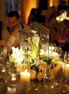 composition florale mariage avec des callas blancs sous cloche en verre, ambiance tamisée et bougies déco
