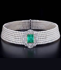 A VERY DECORATIVE ART DECO DOG COLLAR, CIRCA 1926. The central plaque set with a rectangular emerald surrounded by diamonds, mounted on to seven rows of Akoya pearls, mounted in gold and platinum. #ArtDeco #choker #collar