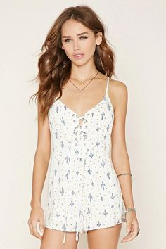 A woven romper featuring an allover floral cactus print, a lace-up V-neckline, adjustable cami straps, a V-cut back, and an invisible back zipper. #f21xmusic