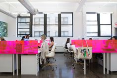 """Custom pink workstation dividers delineate each area, and the ladies are hard at work at desk chairs by <a href=""""http://meelano.com"""" target=""""_blank"""">Meelano</a> ."""