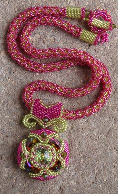 Nefertiti's Treasure.  Website lists stitches.  Necklace: netting around core of herringbone. Peyote and Square Stitch toggle.