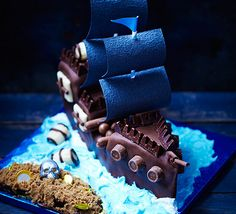Pirate ship and treasure island cake. A stunning children's birthday chocolate cake with hidden treasure buried on a sandy desert island for the kids to dig into