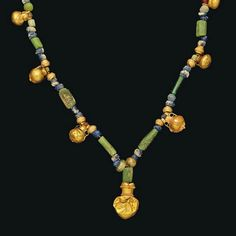 A GREEK GOLD, GLASS, CARNELIAN AND AMETHYST NECKLACE   HELLENISTIC PERIOD, CIRCA 4TH-3RD CENTURY B.C.   Composed of seven gold vessel pendants, interspersed with green glass spherical and tubular beads, blue glass spherical beads, a carnelian and an amethyst spherical beads  13 in. (33 cm.) long max.
