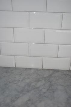 White subway tile with grey grout, grey countertop.
