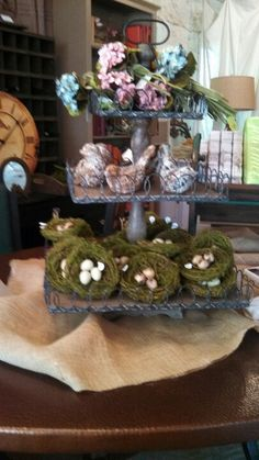 mossy nests filled with eggs, clay birds kama spring flowers in a rustic three tiered stand