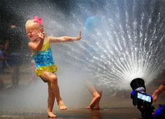 Anne Rowan Slater, 3, dances in the spray of a fire hose at the Hernando Fire Station during the Fireman Splash in Hernando, Miss. Thursday, July 18, 2013. After a short talk about fire safety, over 50 kids were treated to a special cool-off session behind City Hall. (AP Photo/The Commercial Appeal, Jim Weber)