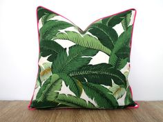 This tropical pillow cover comes in an indoor/outdoor fabric from Tommy Bahama and is water and stain resistant. This print is the smaller version of the original swaying palm print .Colors are shades of green, black yellow and off white and goes perfect with brown outdoor furniture. Ive added a piping in hot pink for some pop. The inner seams are serged for durability and the invisible zipper is hidden on the bottom . Front and back of the outdoor pillow features the same fabric, print may…