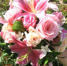 Tear drop bouqet with pink lilies, pink roses, peach roses, and stephanotis stems