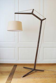 Ein Gestell aus Nussbaumholz und ein schlichter Schirm sind die Gestaltungselemente für Marc Haldemanns Stehleuchte. Als Inspiration für das Gestell diente ein Kran und dementsprechend wird die Kab...