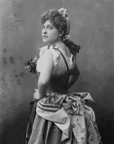 A black-and-white photo of an 1880s actress wearing a bustle