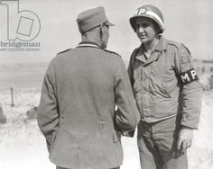 A German prisoner talks with an U.S. soldier probably of the Prisoner of War Escort Guard Company of the 1st Military Police Engineer Special Brigade (ESB). 8th June 1944. Utah Beach, Normandy, France.