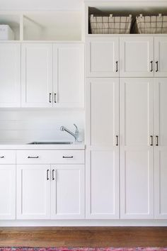 All white laundry room features white shaker cabinets adorned with oil rubbed bronze pulls paired ...