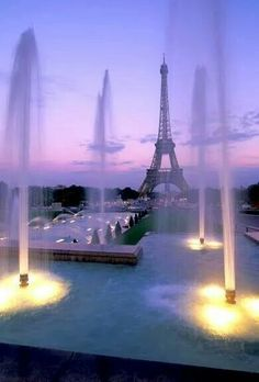 Tall lighted fountains with the Eiffel Tower in the background, the sky painted in a pink and lilac glow of the setting sun. ♡