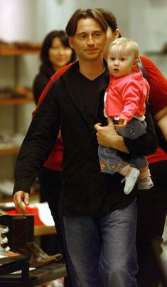 Actor Robert Carlyle holds his daughter Ava while shoe shopping in the SoHo neighborhood May 15 2003 in New York City