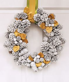 """Use white spray paint to make a """"snowy"""" pine cone wreath.  I like the gold accent color."""