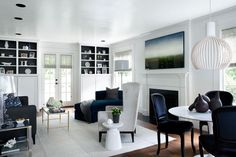 So many great things.  The black back of the shelving.  The velvet chaise.  The painting above the mantle.  The use of white.