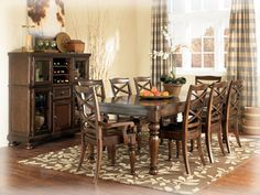 "The warm beauty of the Ashley ""Porter"" dining room collection has a deep finish and ornate details to create an inviting furniture collection for the decor of any dining area. The rich burnished brown finish flows beautifully over the decorative framed details and stylishly turned legs to flawlessly capture the true feel of grand rustic design. With the dark bronze color hardware and beautifully styled scoop saddle seat chairs, the ""Porter"" dining room collection is the perfect choice."
