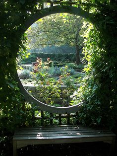 Stunning bench in a garden gazebo that frames the beautiful garden beyond. I love this scene, so pretty!!