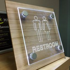 Custom illuminated LED restroom signs are available!  Our satin silver standoffs create a beautiful effect on laser cut clear acrylic.  #custom #signage #led #illumination #bamboo #restroom #sign #office #workplace
