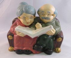 Mom and Pop Coin Bank Old Ceramic Elderly Couple Reading On Sofa---I have a few like this couple...some sitting together and some are individual figurines.