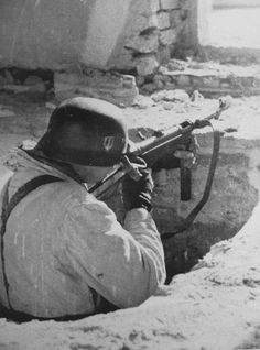 The 3rd battle of Kharkov, a Waffen-SS soldier & his 9mm sub-machine gun (MP40) in combat. 1943, Russia.