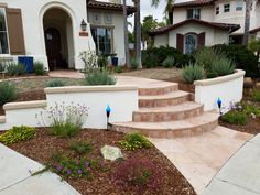 Front entry with low wall stucco wall and curved flagstone walkway with stairs