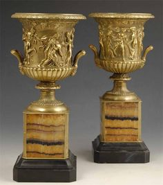 A pair of bronze and blue john mounted vases, modelled on the Borghese vase, the bell shape krater with an ovolo and dart rim to a relief decorated body of a Bacchanalian procession with Dionysus and Ariadne, to a pair of reeded side handles with mask terminals, with a knopped stem and spreading fluted foot, on a blue john panelled and black marble pedestal, 13.25in (33.5cm) h. (2)