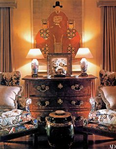 Wing chairs in Lee Jofa fabric stand before an 18th-century French-style chest of drawers. A Grandma Moses painting is displayed on it, a Chinese ancestor scroll above it.
