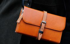 Neutral black and tan combine with attention-grabbing orange in this distressed rectangular handbag.