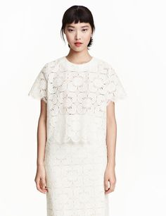 Check this out! Short, wide-cut blouse in lace with short sleeves and an opening at back of neck with button. Unlined. - Visit hm.com to see more.