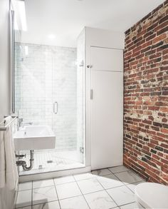 Exposed brick wall mixed with marbled floors and tiled shower. So pretty Bunker Workshop