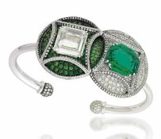 AN EMERALD, DEMANTOID GARNET AND DIAMOND BANGLE -Designed as two conjoined circular panels one centred by an octagonal-cut emerald weighing approximately 6.72 carats to a pavé-set brilliant-cut diamond surround, the other with a portrait-cut diamond centre weighing approximately 5.02 carats to a circular-cut demantoid garnet ground with diamond line detail, raised on a plain polished bangle with diamond sphere terminals.