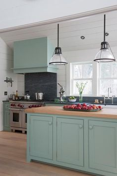 Light blue farmhouse kitchen features light blue cabinets adorned with light blue knobs paired with dark gray stone countertops and shiplap backsplash.