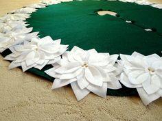 "65"" Christmas Tree Skirt in Glitter Green felt with glitter white poinsettas sewn around the bottom.."